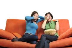 Amis féminins mangeant du maïs éclaté et regardant la TV à la maison Images libres de droits