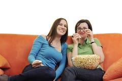 Amis féminins mangeant du maïs éclaté et regardant la TV à la maison Photo stock