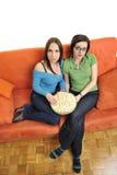 Amis féminins mangeant du maïs éclaté et regardant la TV à la maison Photographie stock