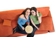 Amis féminins mangeant du maïs éclaté et regardant la TV à la maison Image stock