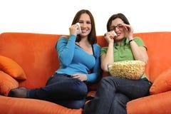 Amis féminins mangeant du maïs éclaté et regardant la TV à la maison Photos stock