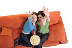 Amis féminins mangeant du maïs éclaté et regardant la TV à la maison Photo libre de droits
