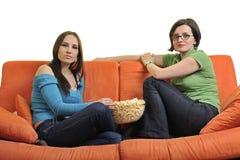 Amis féminins mangeant du maïs éclaté et regardant la TV à la maison Photos libres de droits