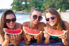Amis féminins mangeant la pastèque Images stock