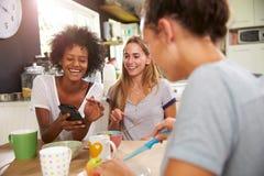 Amis féminins mangeant le petit déjeuner tout en vérifiant le téléphone portable Photos stock