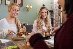 Amis féminins mangeant le repas ensemble dans le restaurant Photographie stock libre de droits