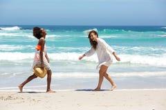 Amis féminins marchant et souriant à la plage Images libres de droits