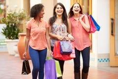 Amis féminins marchant par le mail avec des paniers Image stock