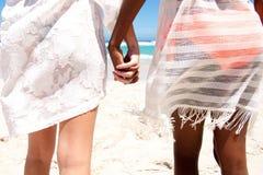 Amis féminins marchant sur la plage Photos stock