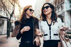 Amis féminins marchant sur la route Image stock