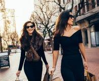 Amis féminins marchant sur la rue de ville avec des paniers Images libres de droits
