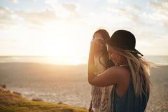Amis féminins marchant sur le bord de mer Photos stock