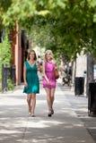 Amis féminins marchant sur le trottoir Photo stock