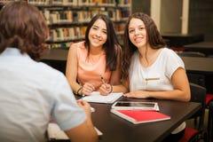 Amis féminins mignons dans une bibliothèque Photos stock