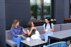 Amis féminins mignons riant et parlant au café, café potable Photographie stock libre de droits