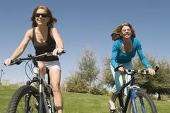 Amis féminins montant des bicyclettes Photographie stock