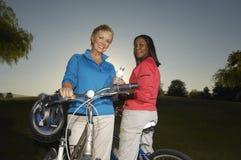 Amis féminins multi-ethniques avec des bicyclettes Photographie stock libre de droits
