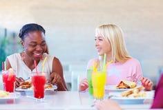 Amis féminins multiraciaux appréciant le repas dans le restaurant Photo libre de droits