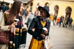 Amis féminins multiraciaux buvant du café extérieur Image libre de droits
