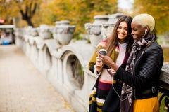 Amis féminins multiraciaux buvant du café extérieur Photos libres de droits