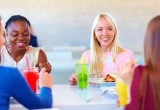 Amis féminins multiraciaux enjoing le repas dans le restaurant Images stock