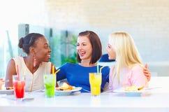 Amis féminins multiraciaux enjoing le repas dans le restaurant Image stock