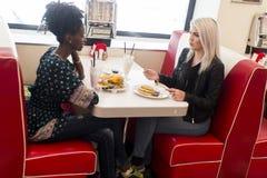 Amis féminins multiraciaux mangeant des aliments de préparation rapide Photo stock