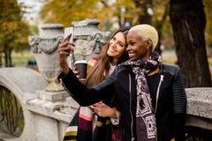 Amis féminins multiraciaux prenant le selfie extérieur Photo libre de droits