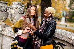 Amis féminins multiraciaux prenant le selfie extérieur Images libres de droits