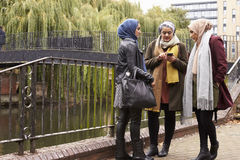 Amis féminins musulmans à l'aide du téléphone portable dans l'environnement urbain Photo stock