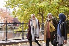 Amis féminins musulmans britanniques marchant dans le milieu urbain Photos stock