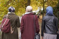Amis féminins musulmans britanniques marchant dans le milieu urbain Image stock