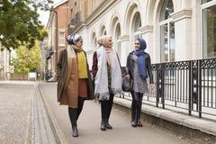 Amis féminins musulmans britanniques marchant dans le milieu urbain Images libres de droits