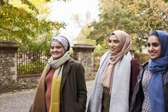 Amis féminins musulmans britanniques marchant dans le milieu urbain Photographie stock