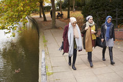 Amis féminins musulmans britanniques marchant par la rivière dans la ville Photos stock