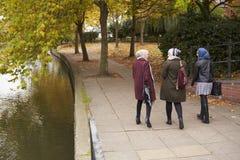 Amis féminins musulmans britanniques marchant par la rivière dans la ville Image stock