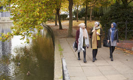 Amis féminins musulmans britanniques marchant par la rivière dans la ville Images stock