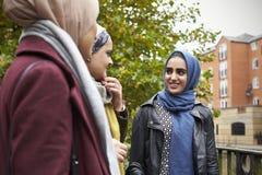 Amis féminins musulmans britanniques se réunissant dans le milieu urbain Photo libre de droits