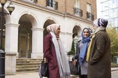 Amis féminins musulmans britanniques se réunissant dans le milieu urbain Images libres de droits