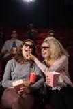 Amis féminins observant le film dans le théâtre Photos libres de droits