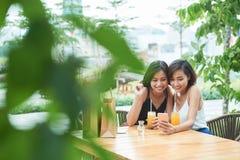 Amis féminins observant les vidéos drôles Photographie stock libre de droits