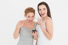 Amis féminins occasionnels choqués avec le téléphone portable Photographie stock