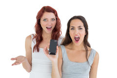 Amis féminins occasionnels choqués avec le téléphone portable Image stock
