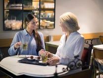 Amis féminins parlant à la table et au sourire de café Images libres de droits