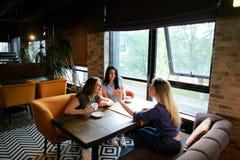 Amis féminins parlant au café et à l'aide du smartphone, café potable Image stock