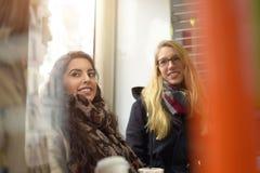 Amis féminins parlant dans l'espace public par la fenêtre Images stock