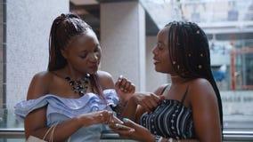 Amis féminins parlant et vérifiant le smartphone au centre commercial clips vidéos