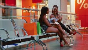 Amis féminins parlant et vérifiant le smartphone tandis que se reposer est centre commercial banque de vidéos