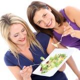 Amis féminins partageant une plaque de salade Photos stock