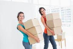 Amis féminins portant des boîtes dedans dans la nouvelle maison Images libres de droits